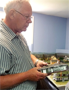 Club member John Cooper with one of the many miniature houses he built from scratch.