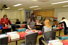 Volunteers wrapping shoe boxes.