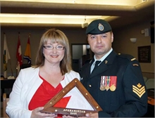 Brenda Daigle receives Canadian Flag from Sgt. Martin Veilleux.