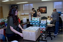 Kelly Matchett, foreground, preparing packages for shipping.